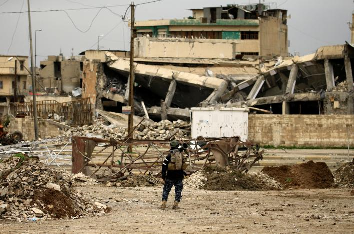A federal policeman carries his weapon as he stands near buildings destroyed in clashes during a battle against Islamic State militants, in Mosul. REUTERS/Thaier Al-Sudani